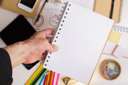 stationery items: Male hand holding blank white spiral notepad above office desktop with blurry electronic devices and other stationery items. Mock up
