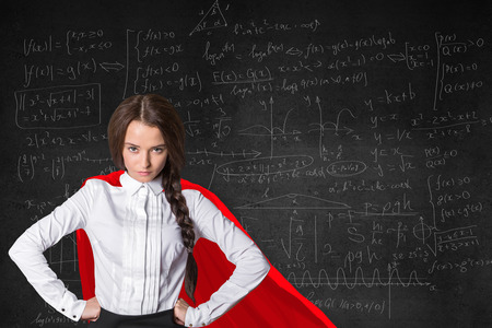 knowledge is power: Pretty confident superwoman with red cape on mathematical formulas background. Knowledge power concept