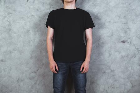 コンクリートの壁の背景に空の黒いシャツの若い男の子のフロント ビュー。モックアップします。