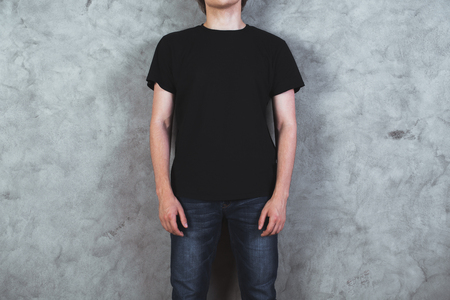 Front view of young boy in empty black shirt on concrete wall background. Mock up 스톡 콘텐츠