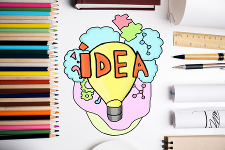 Top view of workplace with colorful supplies and creative light bulb sketch. Idea concept