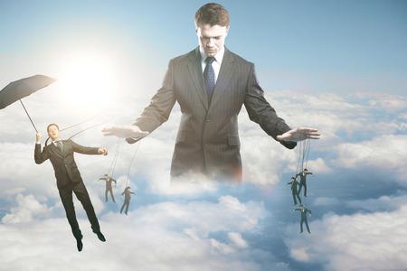 Nachdenkliche junge Geschäftsmann Untergebenen am Himmel Hintergrund mit Sonnenlicht zu manipulieren. Steuerungskonzept