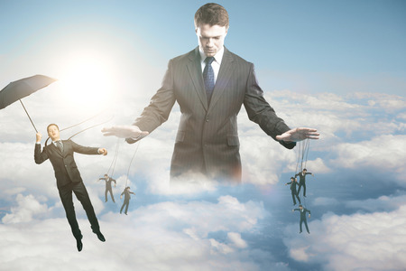 Nachdenkliche junge Geschäftsmann Untergebenen am Himmel Hintergrund mit Sonnenlicht zu manipulieren. Steuerungskonzept Standard-Bild