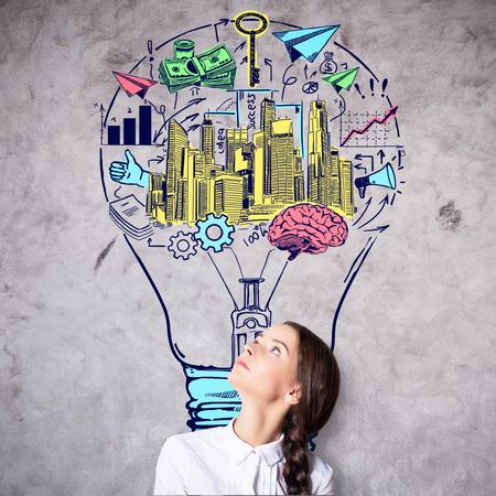 idea sketch: Attractive caucasian businesswoman on concrete background with creative colorful business sketch inside light bulb. Idea concept