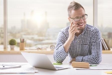 Portrét pohledný mladý muž v brýlích sedí u kanceláře s přenosným počítačem a mluvit na mobilním telefonu. Komunikační koncept Reklamní fotografie