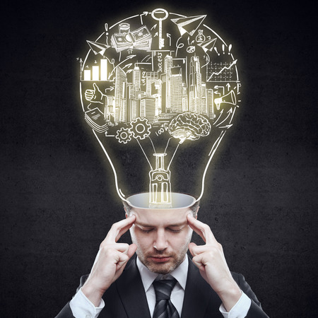 idea sketch: Pensive businessman with abstract business sketch inside light bulb head on dark background. Idea concept