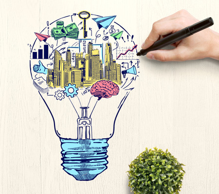 Hand drawing creative colorful business sketch inside light bulb on wooden desktop with plant. Idea concept Stock Photo