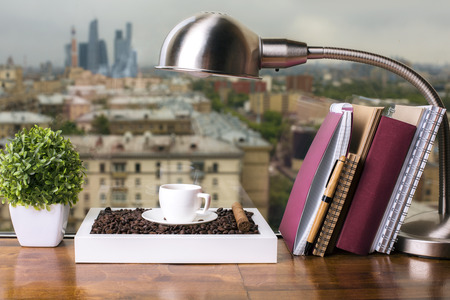 home office desk: Closeup of wooden windowsill with coffee cup and beans, table lamp, decorative plant and books with notepads on city background