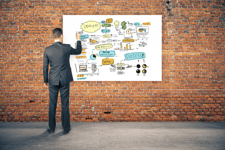 standing man: Back view of young businessperson drawing business sketch on whiteboard hanging in red brick interior. Success concept. 3D Rendering