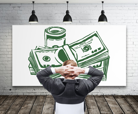 interior walls: Relaxing young businessman looking at creative dollar bill sketch in modern interior with white brick walls, wooden floor and ceiling lamps. Financial growth and success concept. 3D Rendering