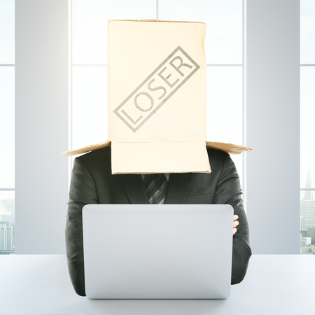 expressing negativity: Cardboard box with loser stamp on the head of a businessperson using laptop at workplace. Failure concept. 3D Rendering
