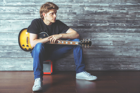 young guy: Handsome young guy with electric guitar sitting on amplifier in wooden room. Music, concert rehearsal concept Stock Photo