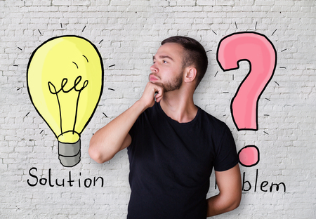 thoughtful: Thoughtful young man with light bulb and question mark sketches on white brick wall background. Solution concept
