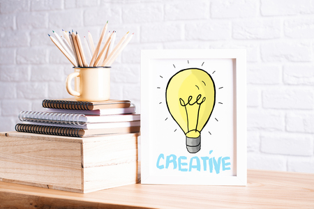 Workplace with light bulb sketch in small picture frame, stack of notepads and iron mug with pencils on white brick wall background. Creative idea concept Stock Photo
