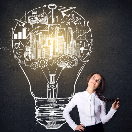 idea sketch: Attractive caucasian girl on concrete background with creative business sketch inside light bulb. Idea concept Stock Photo