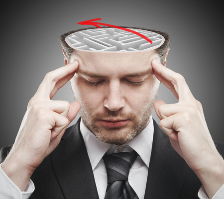 Thoughtful young businessman with abstract concrete maze and red arrow inside head. Brainstorm concept