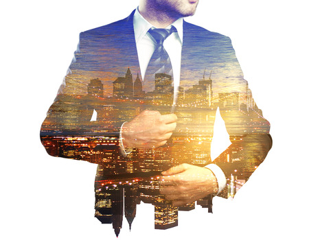 Young businessman in suit on creative city background with sunlight. Double exposure