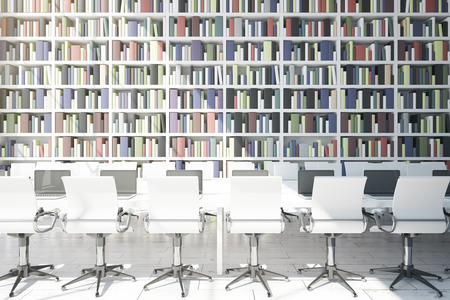 law library: Front view of long white table with laptops and chairs on huge bookcase background. Library concept. 3D Rendering Stock Photo