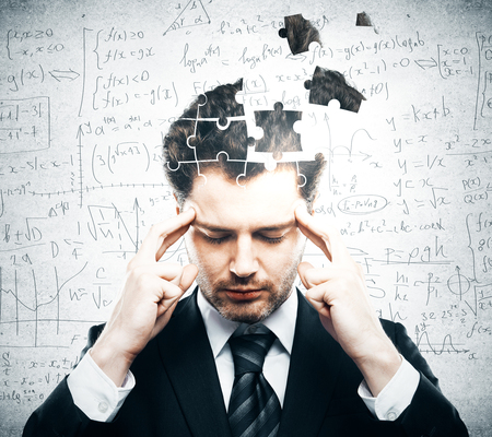 business puzzle: Portrait of pensive young businessman with puzzle piece head on grey background. Business challenge concept