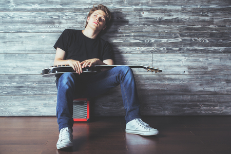 Handsome young man with electric guitar sitting on amplifier in wooden room. Music, concert rehearsal concept Banque d'images