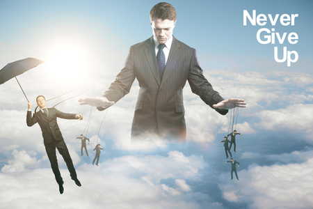 manipulating: Pensive young businessman controlling subordinates on sky background with sunlight. Manipulation concept
