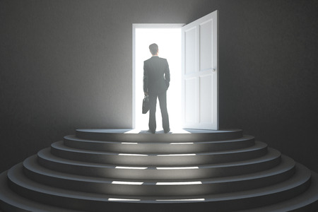 heaven: Back view of young businessman standing in abstract concrete interior with stairs and open door with bright light. Success concept Stock Photo