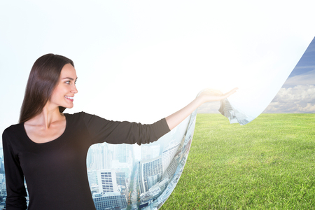 nature woman: Smiling young woman dragging abstract cloth with city image and revealing green meadow. Eco and nature concept