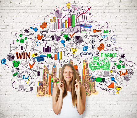 crossed fingers: Pretty caucasian girl with crossed fingers standing against white brick wall with creative colorful business sketch. Success concept