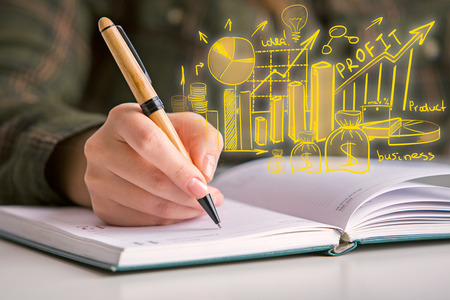 Close up of hand writing in notepad with abstract financial sketch. Business planning concept Stock Photo