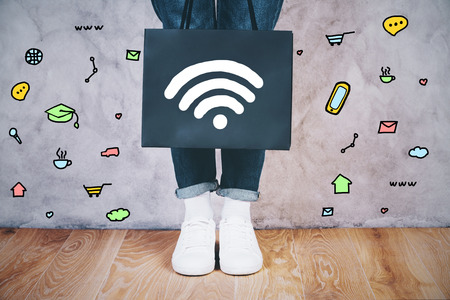 female legs: Close up of female legs with wifi signal icon on shopping bag and communication icons around on concrete wall. Social media concept