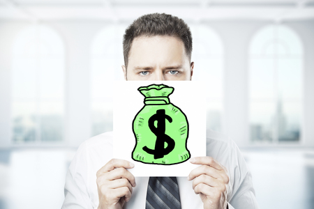 wealth concept: Frowning young businessman holding poster with drawn money bag. Wealth concept