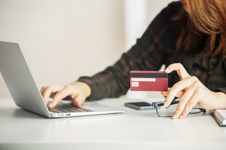 Woman holding credit card while using laptop and cellphone on white desktop. Online payment concept Imagens - 65555897