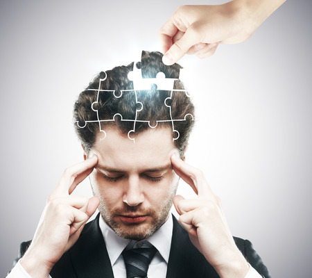 Hand adding last piece to pensive puzzle headed businessman on grey background. Business challenge and solution concept Banco de Imagens - 65553033