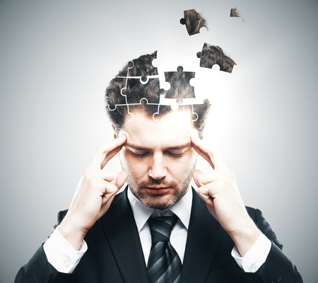 science education: Portrait of pensive young businessman with puzzle piece head on grey background. Business challenge concept