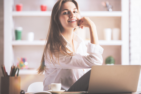 charming girl: Portrait of charming caucasian girl sitting at office desk with laptop, coffee cup, supplies and other items