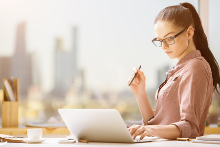 item: Portrait of beautiful lady using laptop at workplace. Project concept Stock Photo