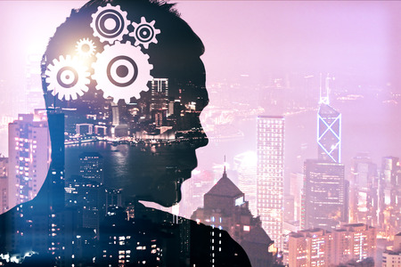 innovation concept: Silhouette of thoughtful young man with gears in head on illuminated night city background. Double exposure. Brainstorming concept