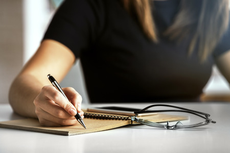Girl writing in spiral notepad placed on white desktop with glasses and smartphone. Close up