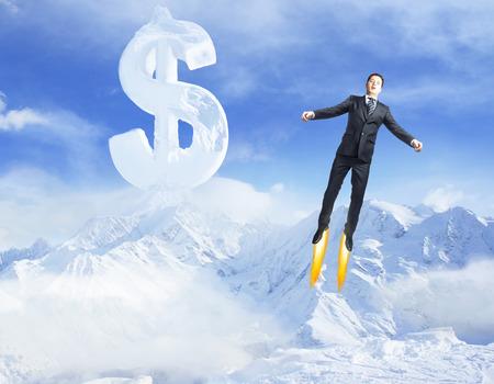 Jovem que voa em céu azul brilhante com sinal de dólar criativo acima de montanhas nevadas. Conceito de sucesso Imagens