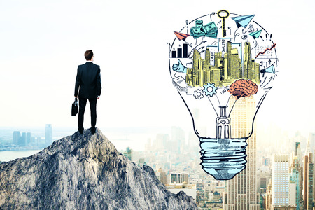 creative idea: Back view of young businessman standing on mountain top next to creative financial sketch inside light bulb. Business idea and leadership concept Stock Photo