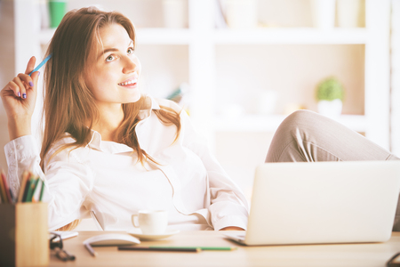 Portrait of cute european female sitting at office desk with laptop, coffee cup, supplies and other items