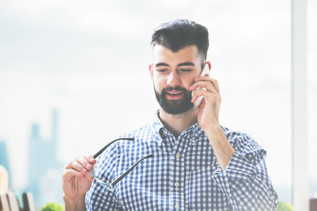 1: Close up portrait of happy caucasian guy talking on cellphone Stock Photo