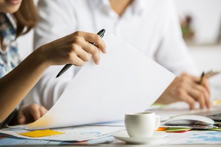 Nahaufnahme der kaukasischen Mann und Frau Papierkram mit Kaffeetasse auf unordentlich Tisch zu tun. Teamwork work~~POS=HEADCOMP-Konzept Standard-Bild - 65980512