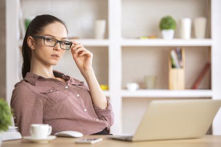 gefesselt: Nette kaukasischen Frau in ihrem Büro Schreibtisch sitzt mit Laptop, dekorative Pflanze und andere Gegenstände, schaut in die Kamera