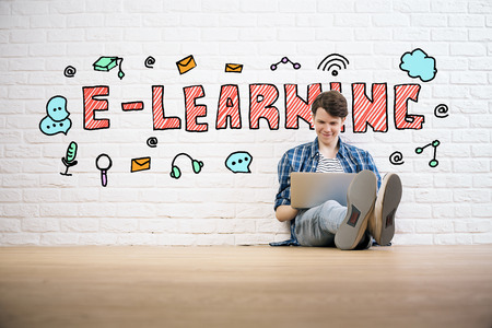 wood floor: Young man using laptop in white brick room with education sketch. E-learning concept