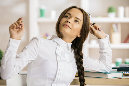 Portrait of pretty daydreaming woman with pen at workplace