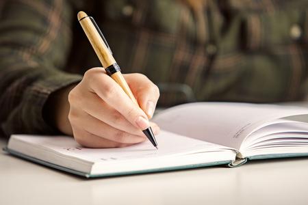 Gros plan d'une main de femme écrivant dans l'organisateur