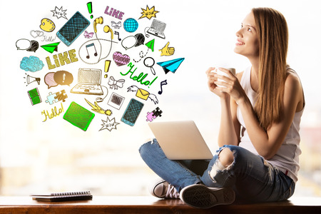 cloud computer: Happy young woman with creative social media icons, laptop and coffee cup.