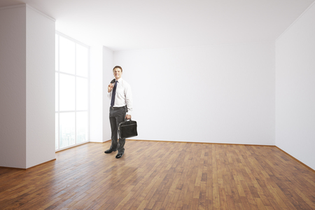 unfurnished: Businessman in unfurnished interior with blank wall