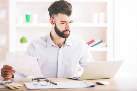 Portrait of handsome european male doing paperwork in office